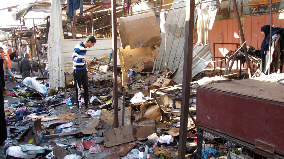 People stand among debris at the site of a bomb attack at a marketplace in Baghdad's Doura District